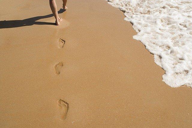 Človek s bosými nohami kráčajúci po piesočnatej pláži