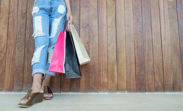 Žena vo vysokých podpätkoch s nákupnými taškami v rukách