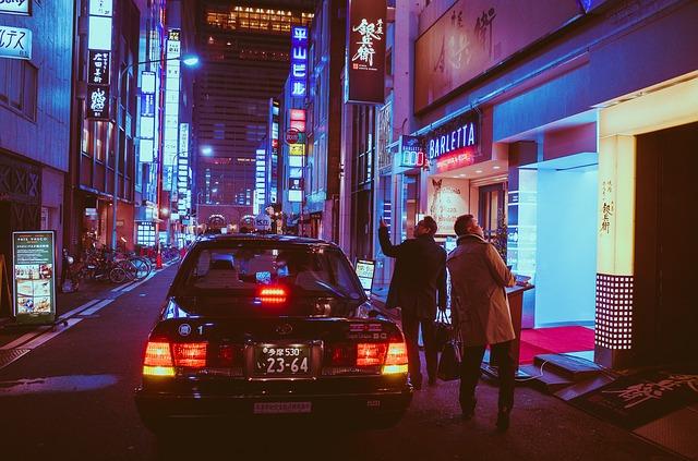 Dvaja muži nastupujú do auta zaparkovaného na rušnej ulici
