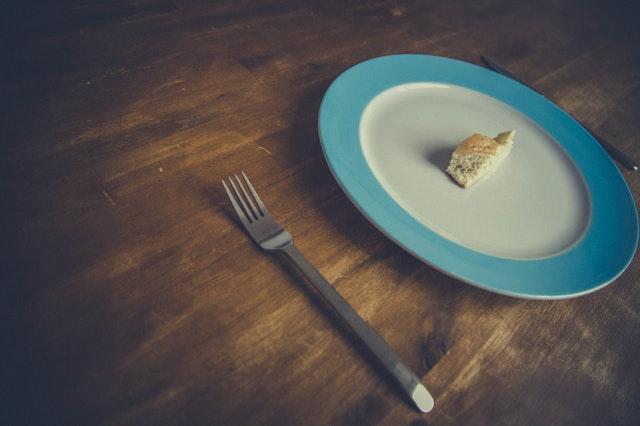 Tanier s malým kúskom jedla a vidlička položené na tmavom drevenom stole