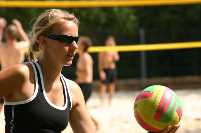Žena v čiernych okuliaroch a v čiernom tričku hrá plážový volejbal