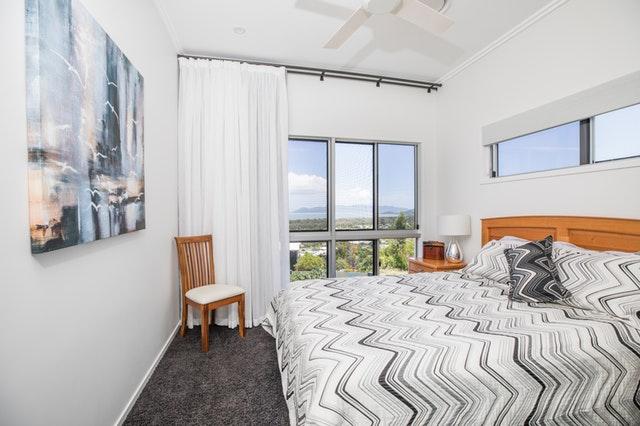 Veľká manželská posteľ v spálni umiestnená pod veľkým oknom