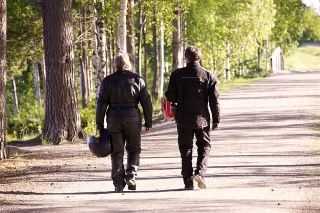 Dvaja motorkári idú peši, park, les.jpg
