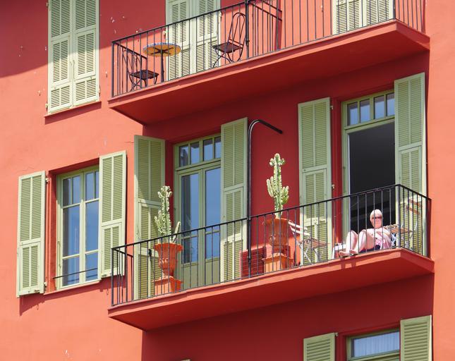 Balkón so zábradlím, na ktorom sedí žena.jpg