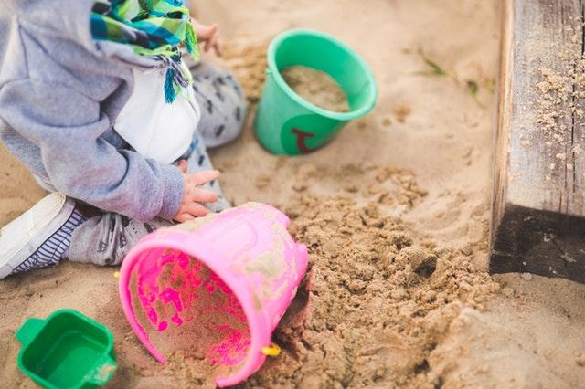 Dieťa sa hrá s formičkami v piesku.jpg