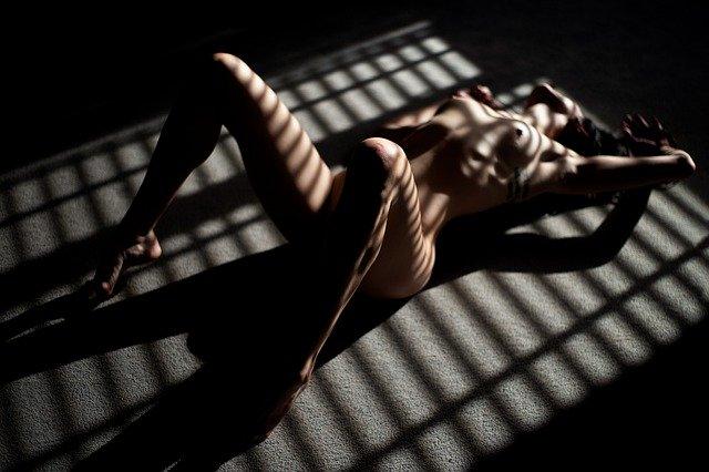 Nahá žena leží na zemi v tieni žalúzií