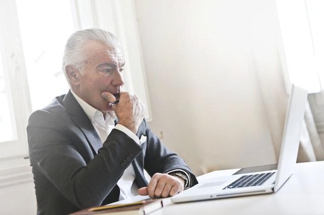 Starší zamyslený muť hľadí do laptopu, oblek, ponikateľ